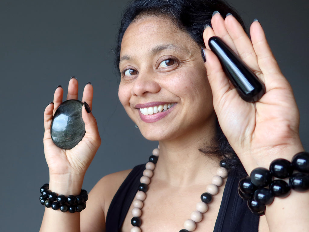 Sheila of Satin Crystals wearing Obsidian jewelry holding an Obsidian palm stone and massage wand