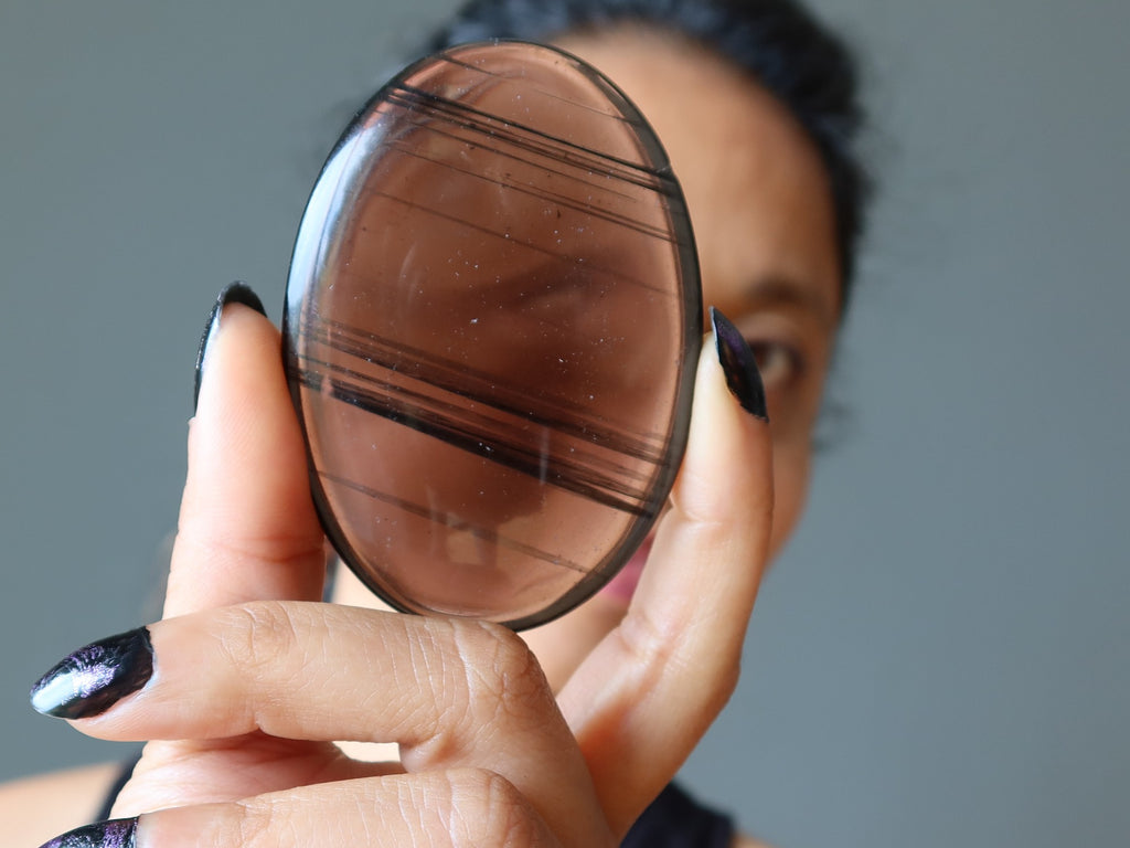 Sheila of Satin Crystals looking through a midnight lace obsidian stone
