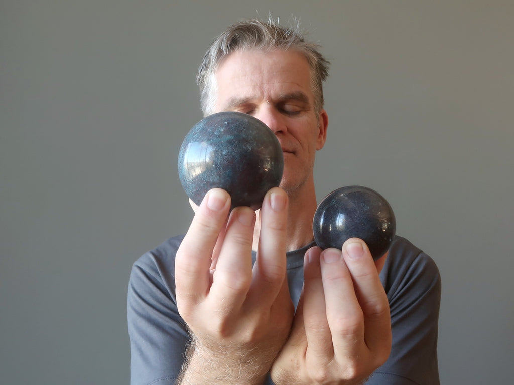 man with eyes closed holding two ruby kyanite spheres