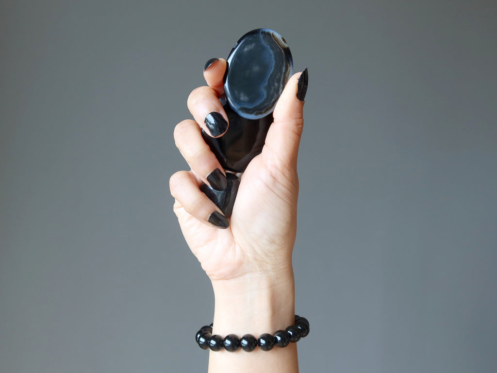 hand wearing black onyx bracelet and holding onyx crystals