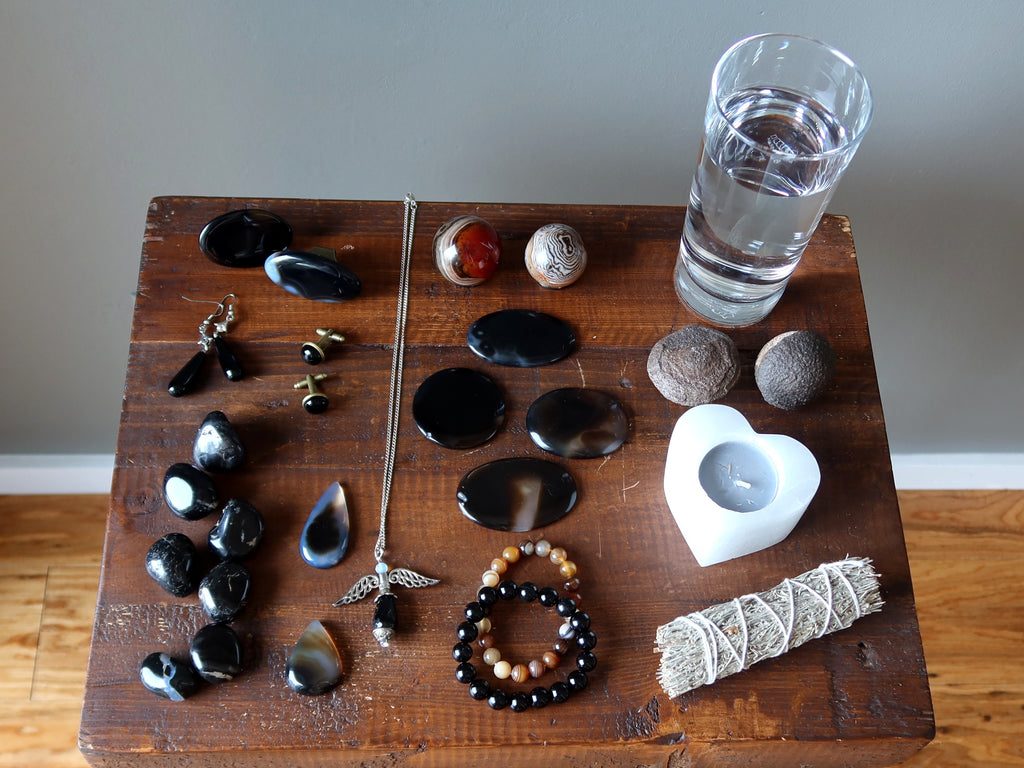 table full of onyx crystals and jewelry, moqui marbles, candle, sage, water