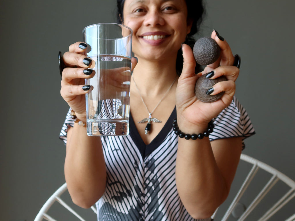 sheila of satin crystals holding a glass of water and pair of moqui marbles