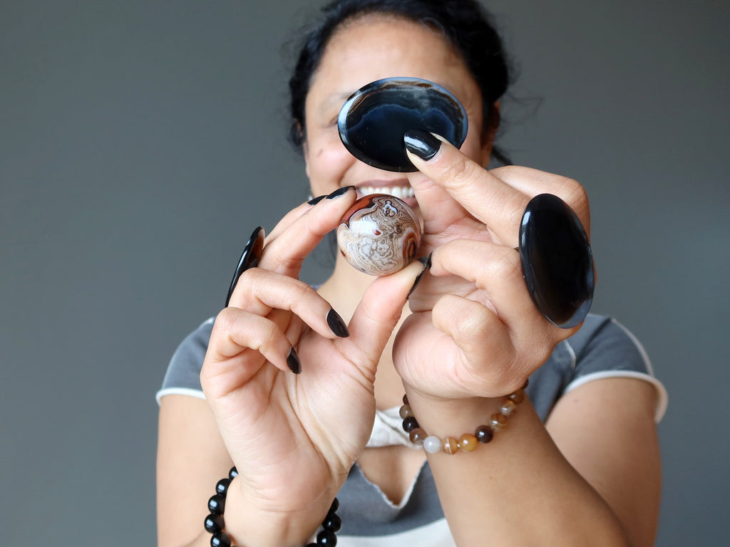 female holding and wearing onyx and sardonyx crystals