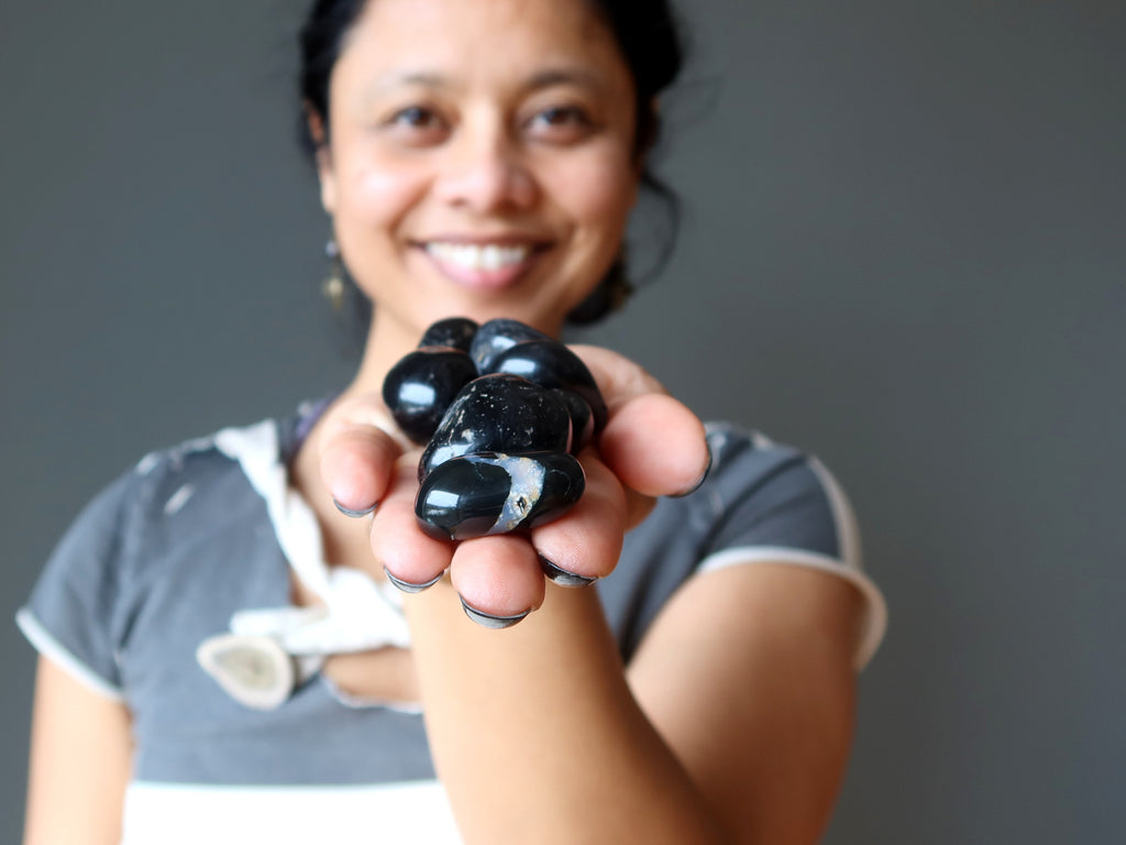 sheila of satin crystals holding a pile of black and white onyx tumbled stones