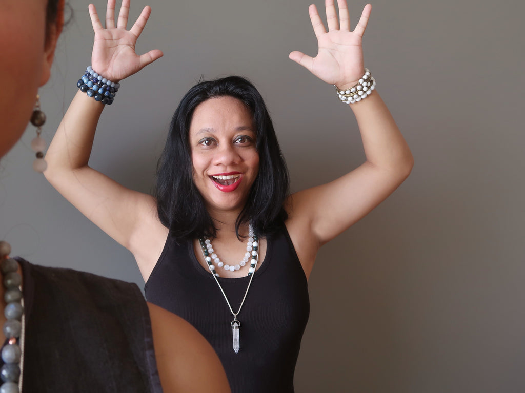 Lisa of Satin Crystals with hands up, smiling with jewelry on against gray wall