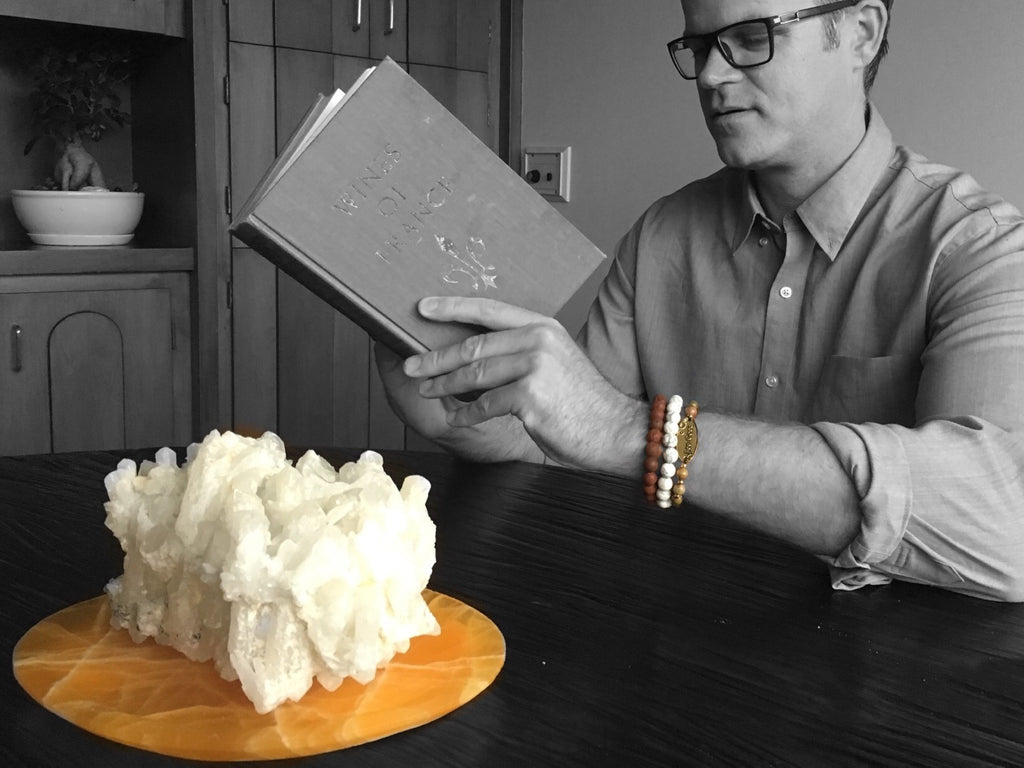 Man Reading at a round table with a Quartz cluster centerpiece - Crystal Healing Information