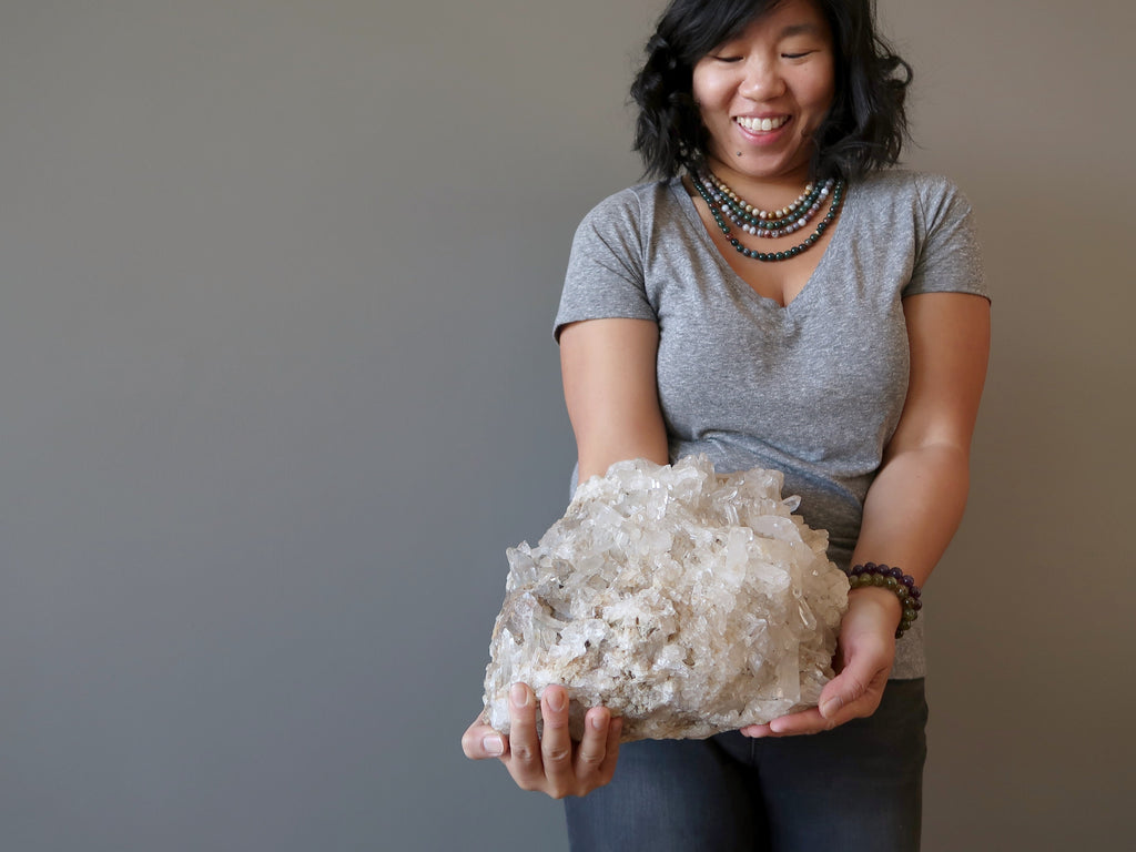 Large Quartz cluster held by female mode against gray background at Satin Crystals Shop