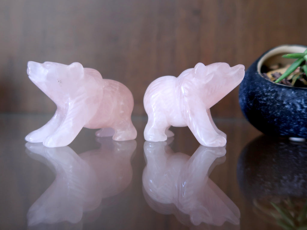 A pair of pink Rose Quartz bear stone figurines on a glass shelf at the Satin Crystals boutique