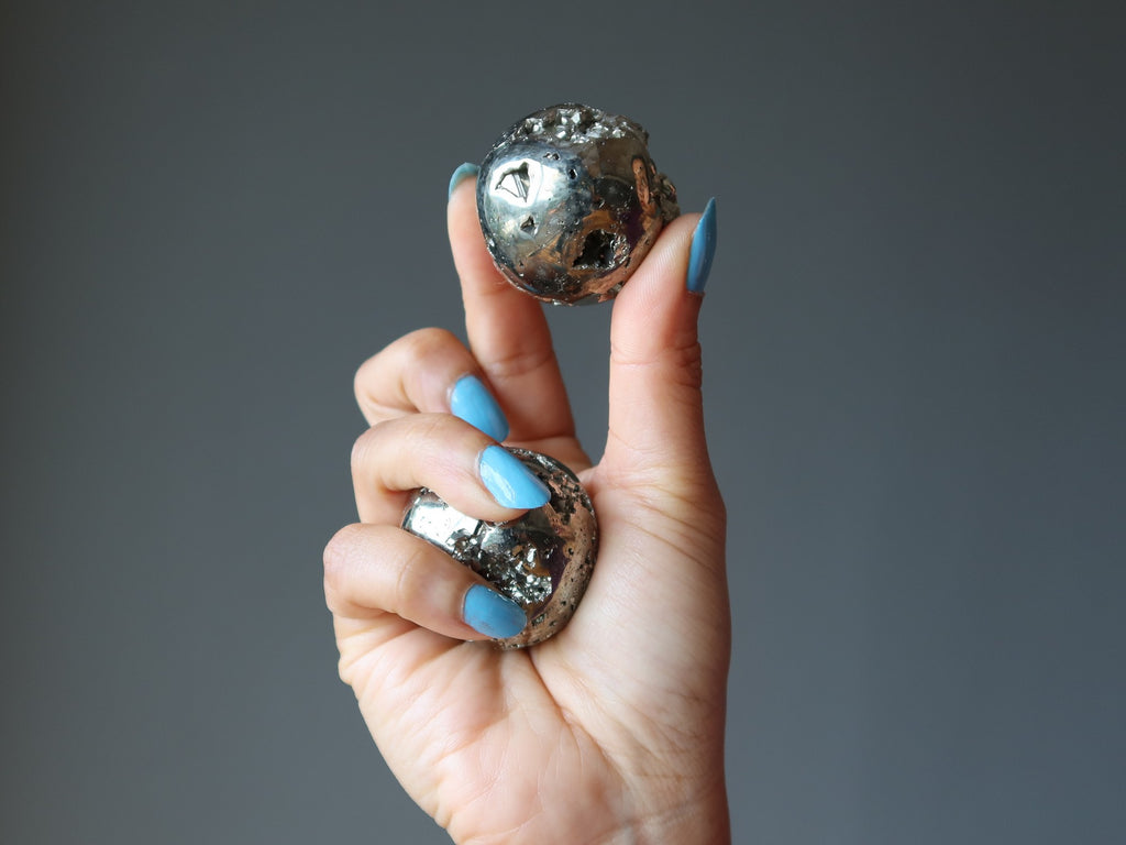 hand holding pyrite spheres