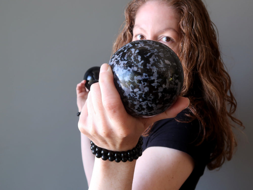 jamie of satin crystals holding up a gabbro crystal healing ball sphere