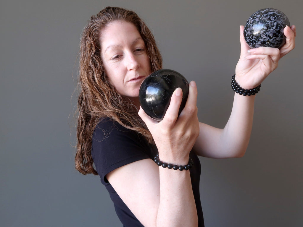 jamie of satin crystals holding up a black tourmaline and gabbro stone sphere for protection