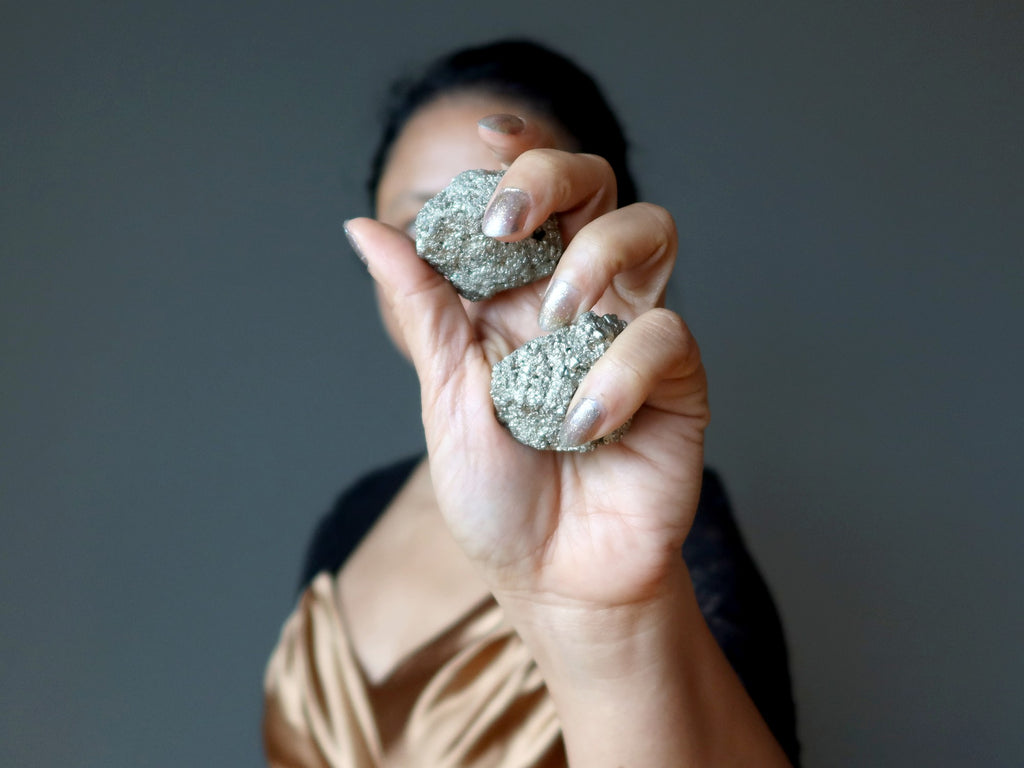 female holding two raw pyrite stones in her hand