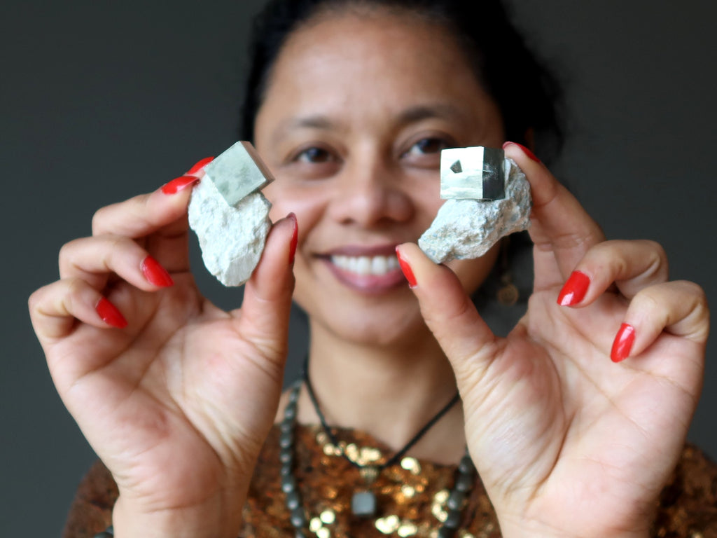 sheila of satin crystals holding two pyrite cubes in white matrix