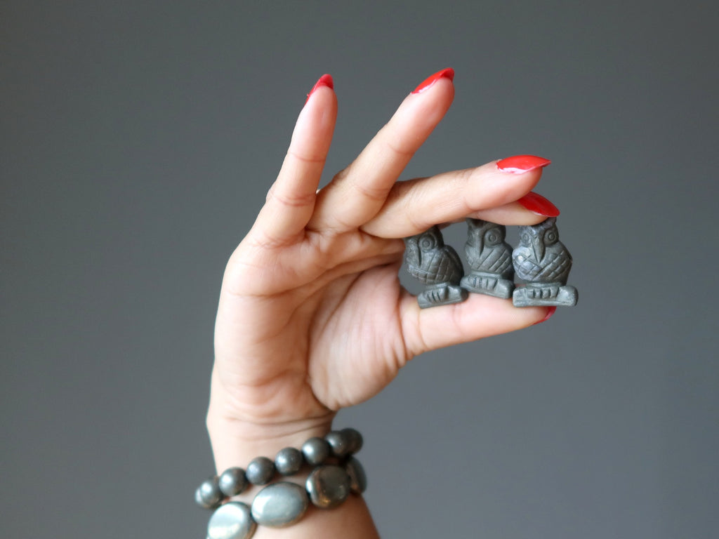 hand wearing pyrite bracelets holding three pyrite owl carvings