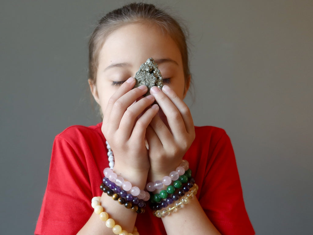 female child meditating with pyrite cluster
