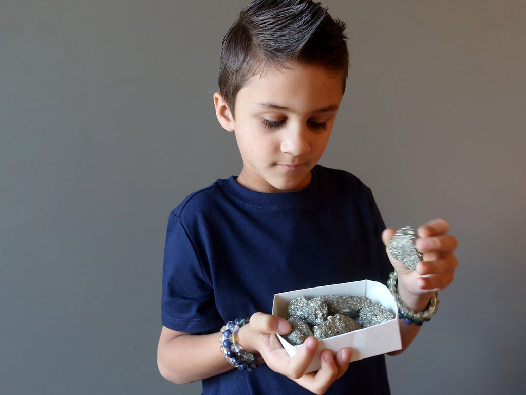 male kid choosing from a box of pyrite clusters