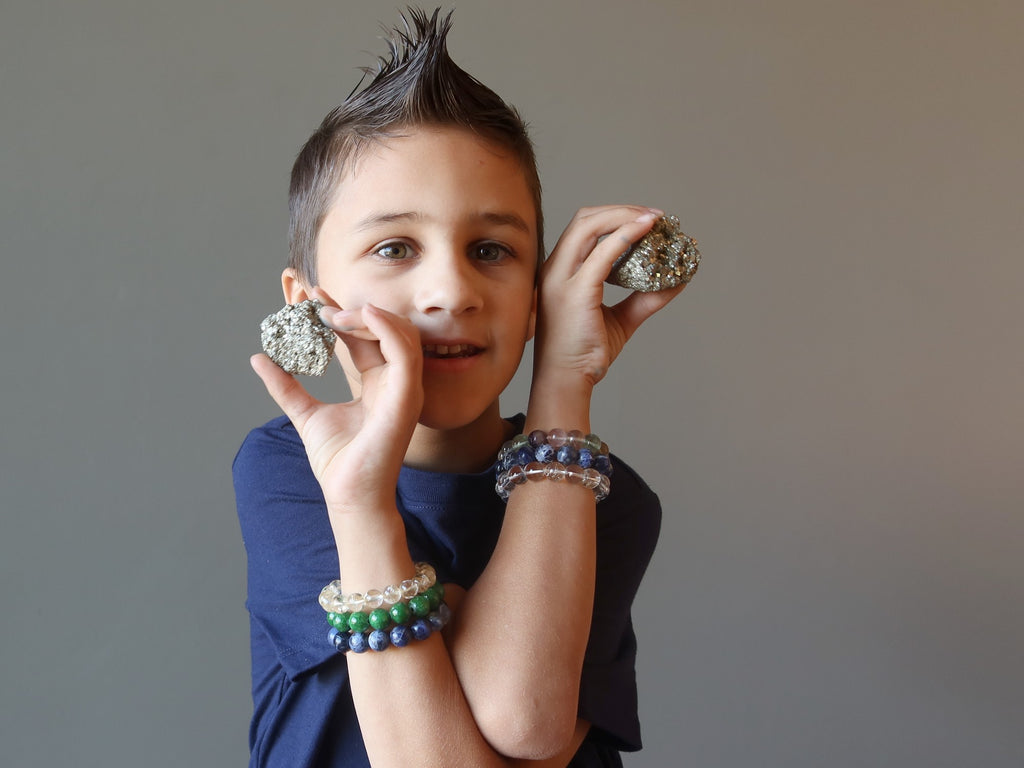 male child holding two pyrite clusters