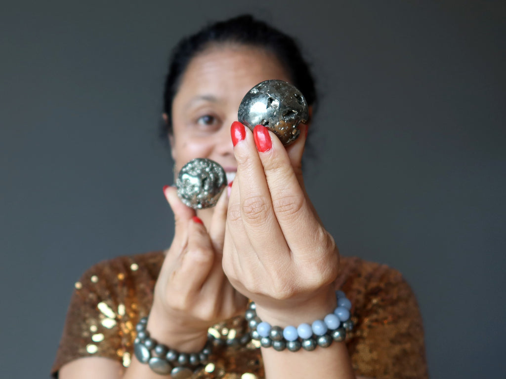 sheila of satin crystals holding two pyrite spheres