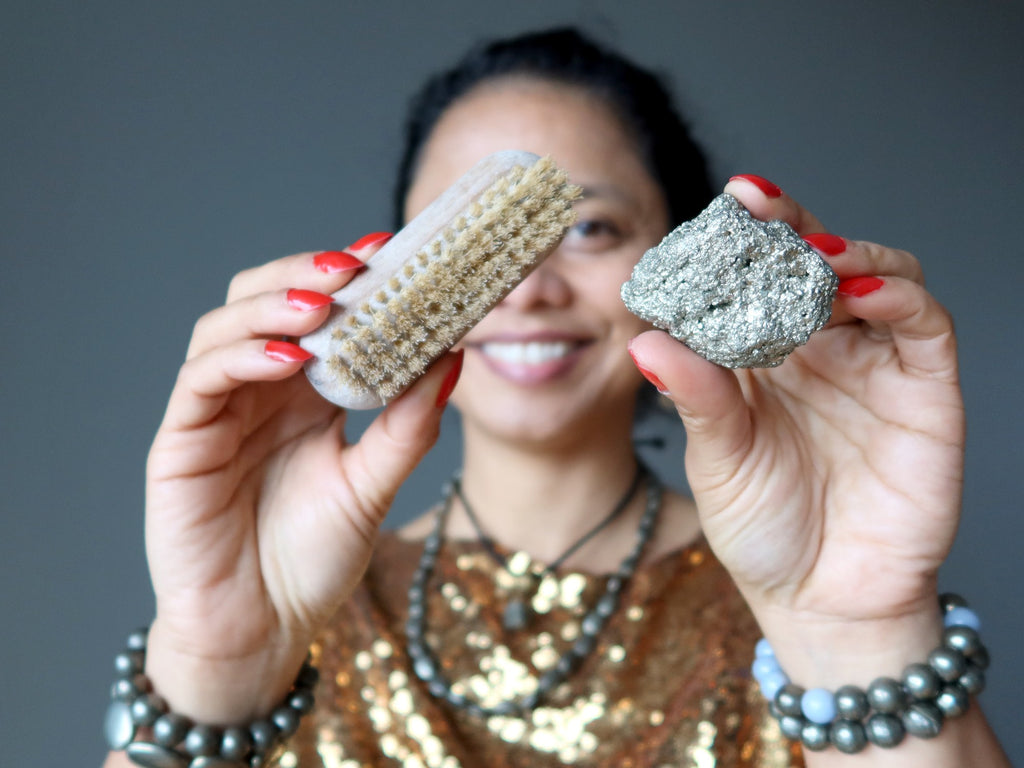sheila of satin crystals holding a scrub brush and a pyrite cluster