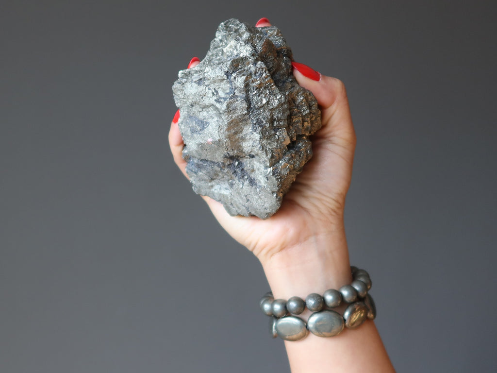 hand wearing pyrite bracelets carrying a pyrite cluster