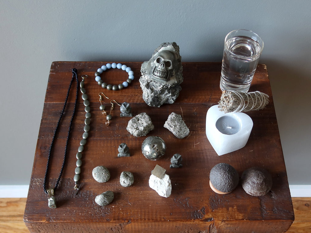 a wood table with pyrite jewelry, stones, water, candle, sage, and moqui marbles