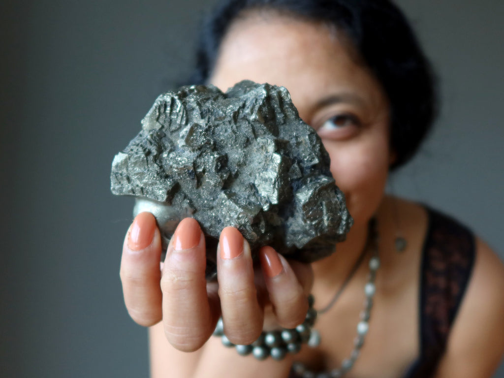 sheila of satin crystals holding out a large pyrite cluster