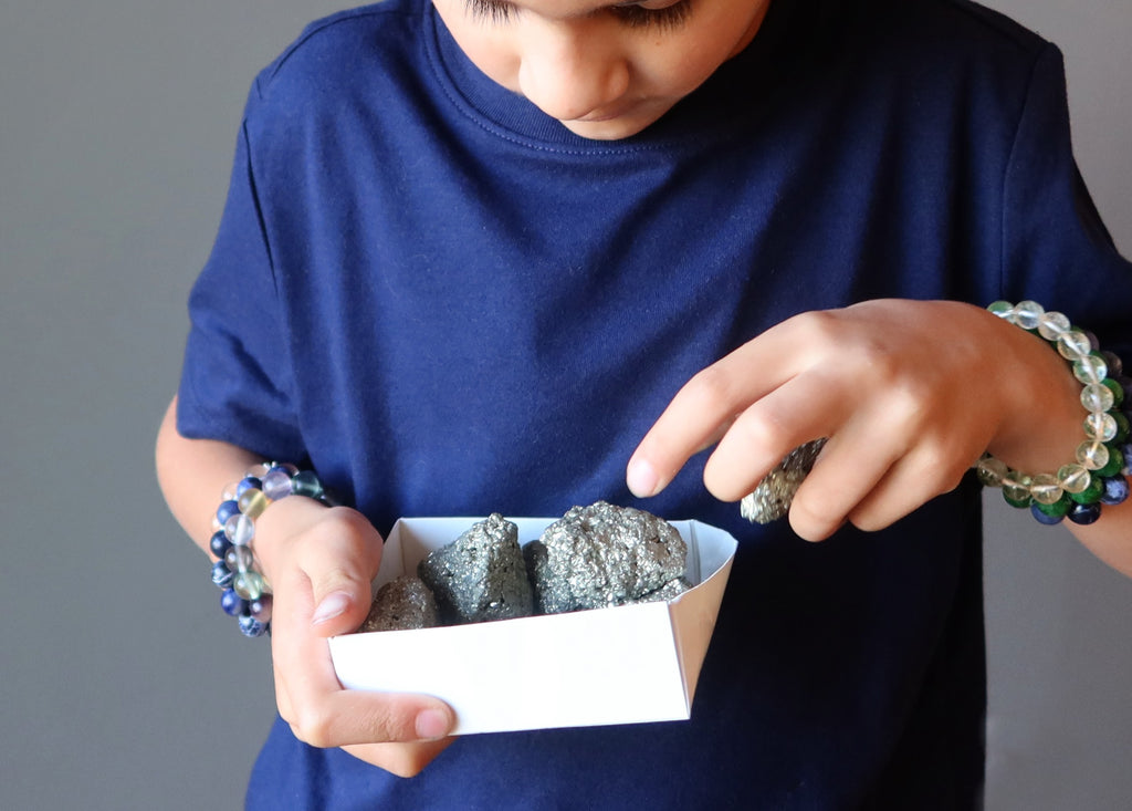 boy picking out pyrite clusters from a box
