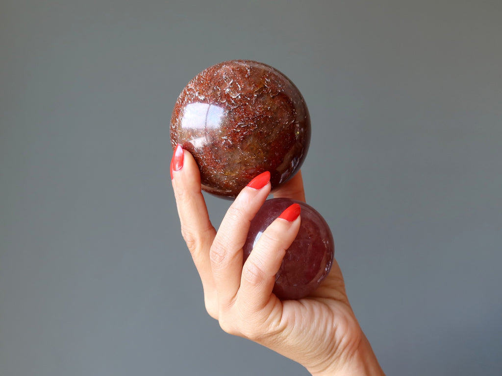 hand holding two red quartz spheres