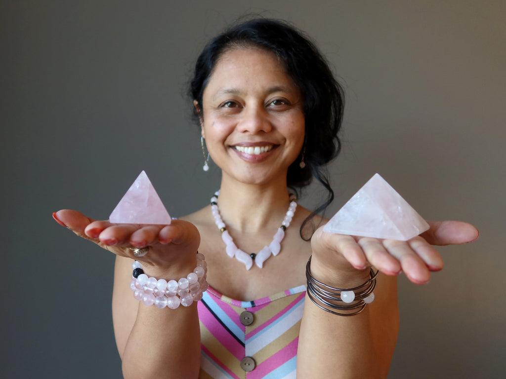 sheila of satin crystals holding two rose quartz pyramids in her palms