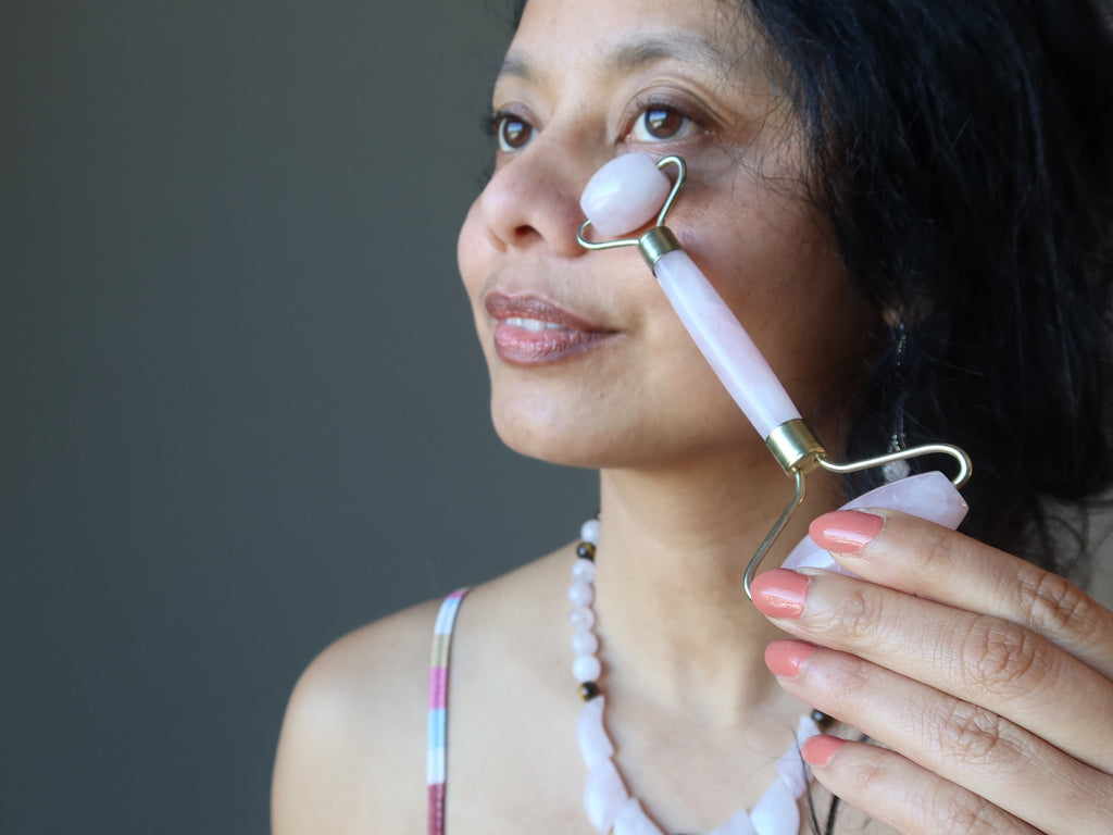 sheila of satin crystals using a rose quartz facial roller on her face