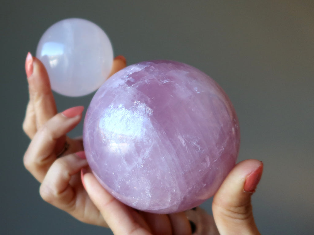 hands holding up a pale pink and a dark pink rose quartz sphere