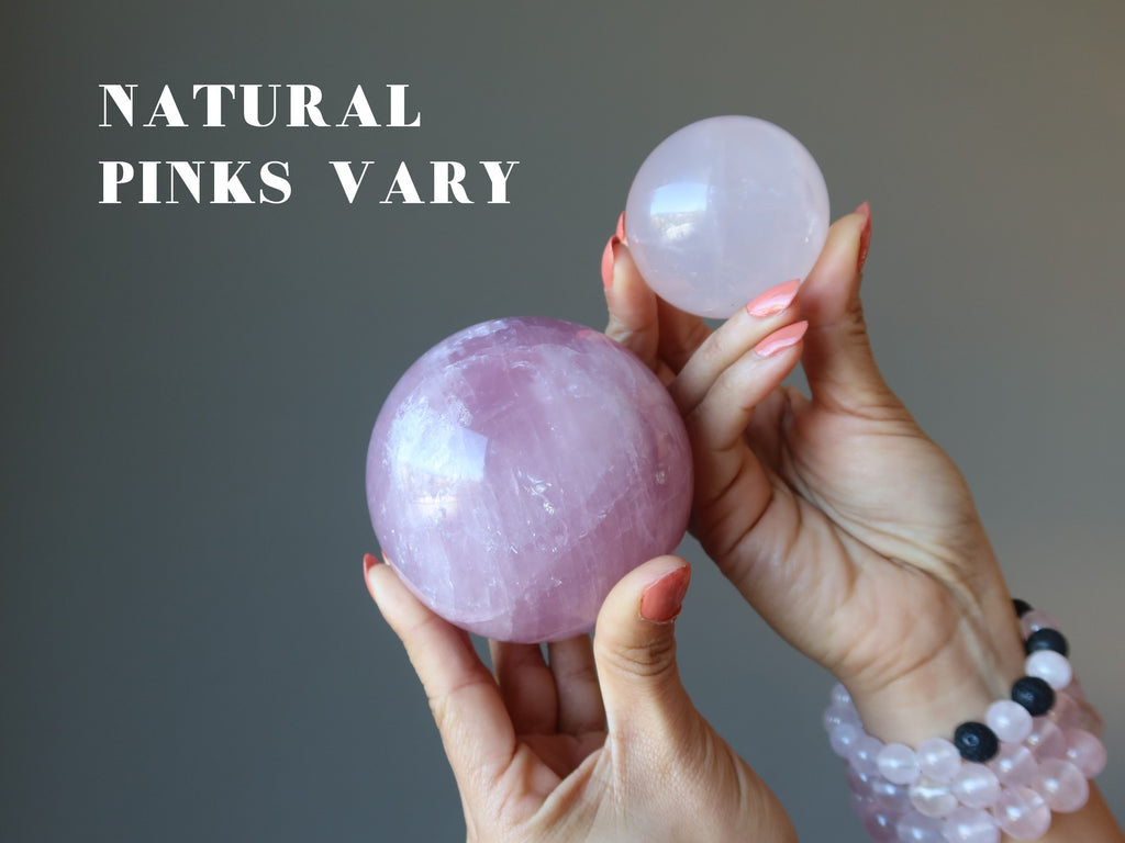 hands holding up a dark pink and a light pink rose quartz sphere to show natural pinks vary