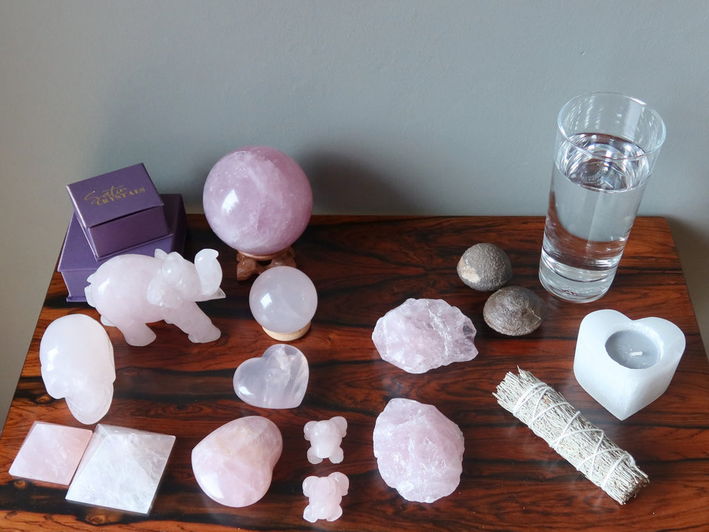 rose quartz crystals, moqui stones, candle, sage, water on a table