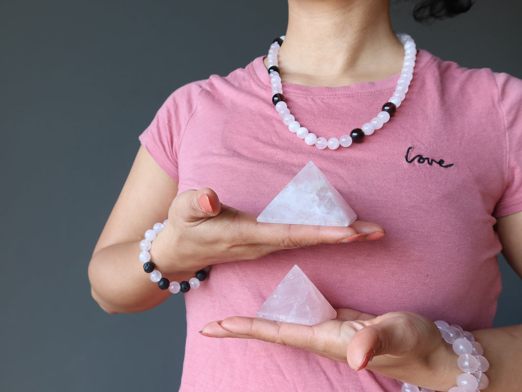 female in pink shirt wearing rose quartz jewelry and holding two pyramids