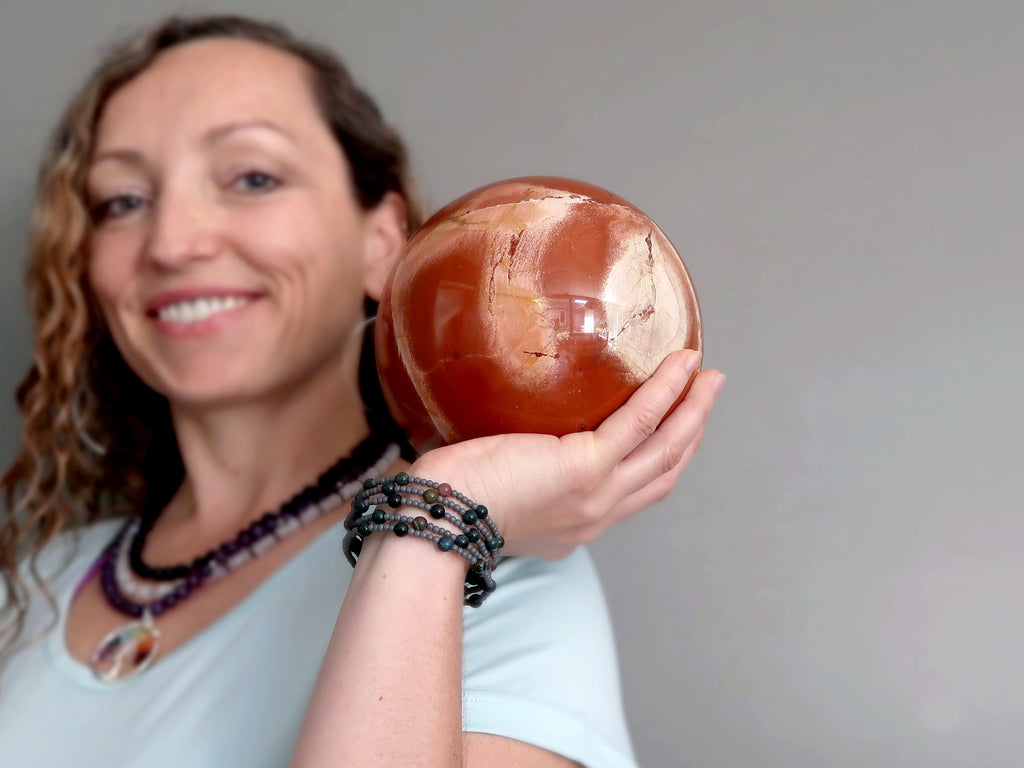 model holding up a large red jasper ball in one hand at satin crystals boutique