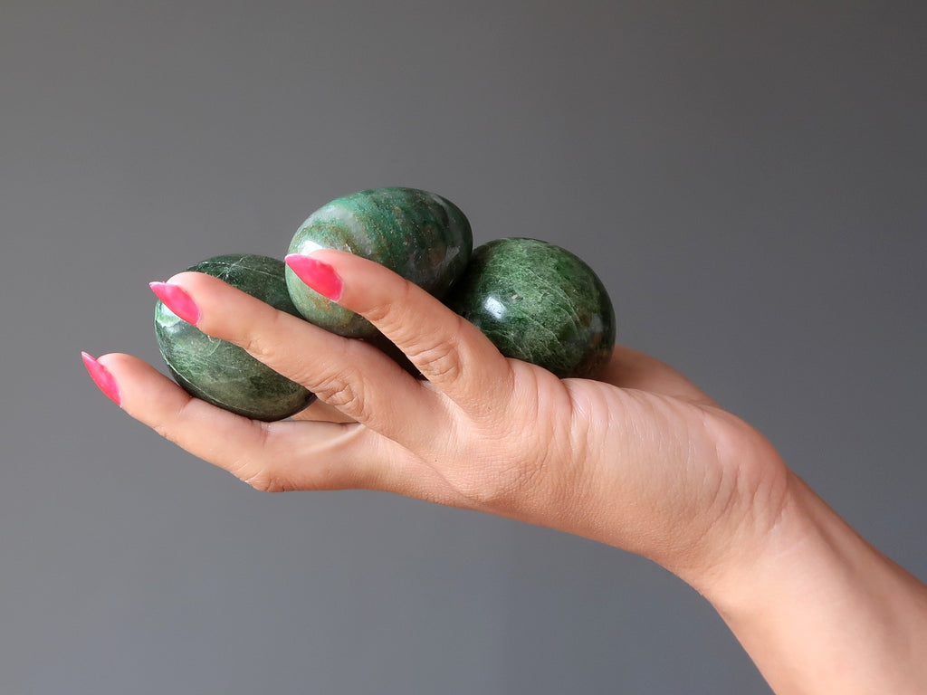 hand holding three green diopside stone eggs