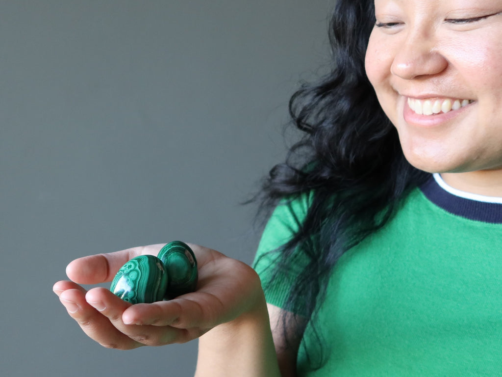 jessica of satin crystals looking down at her hand holding two malachite eggs