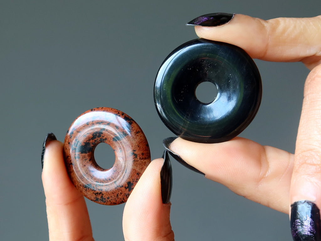 hands holding a mahogany and a black obsidian donut stone