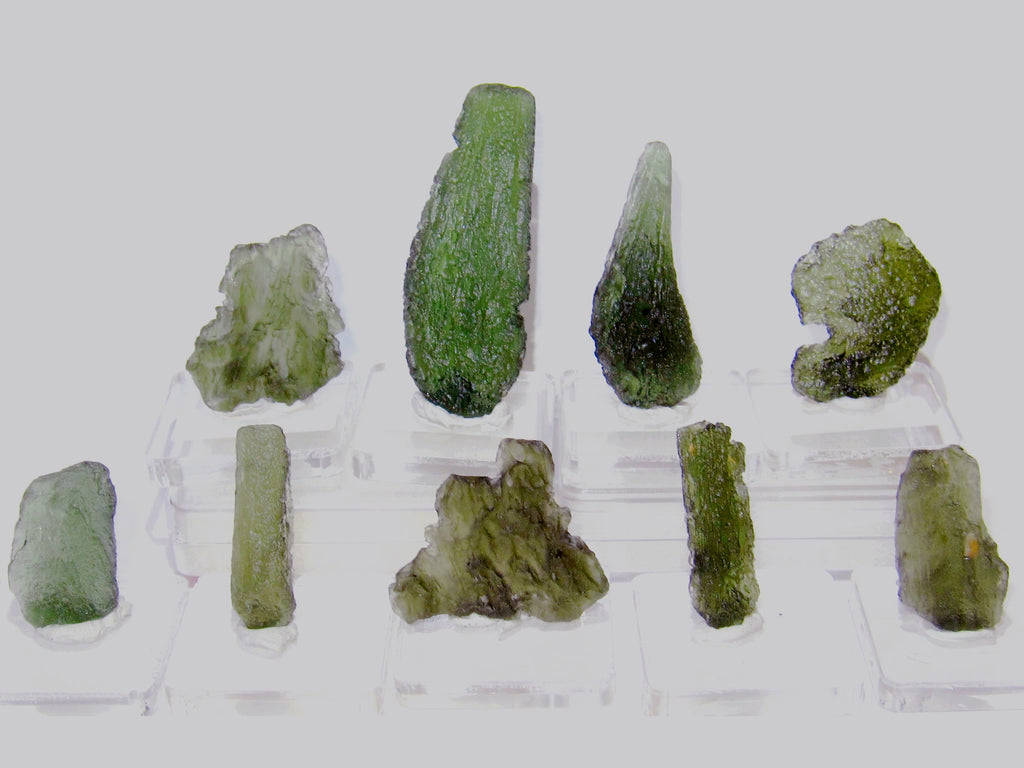 Displayed collection of 9 moldavite meteorites at satin crystals