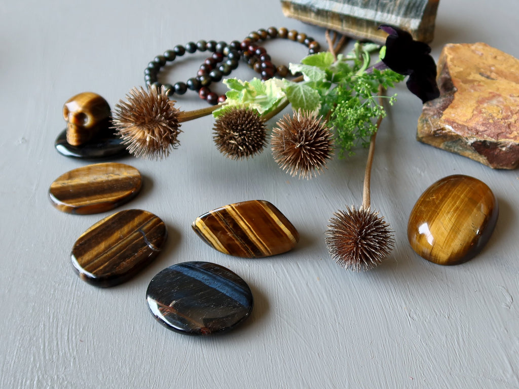 a selection of tigers eye stones and greenery