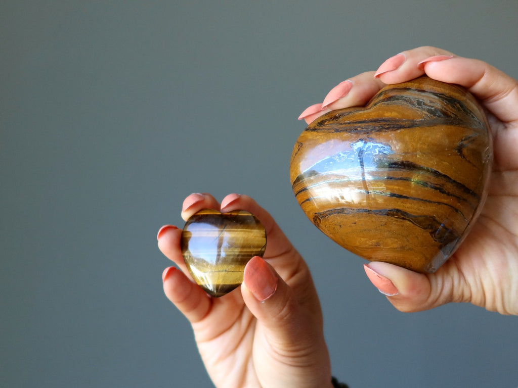 hands holding two tigers eye hearts