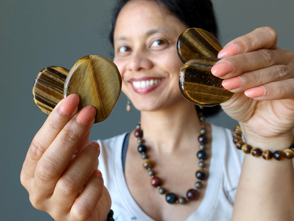 sheila of satin crystals holding four tigers eye palm slabs