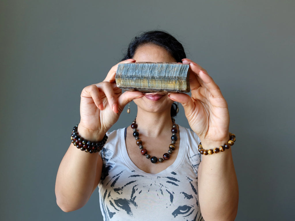sheila of satin crystals wearing tigers eye jewelry and holding a raw tigers eye in front of her face