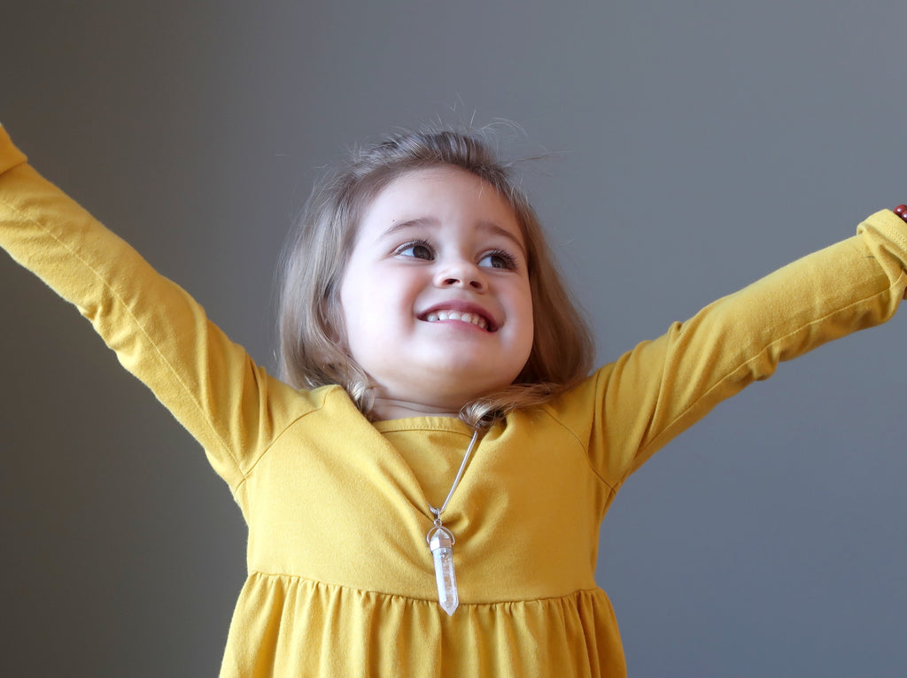 happy young girl in a yellow dress with her hands in the air wearing satin crystals jewelry
