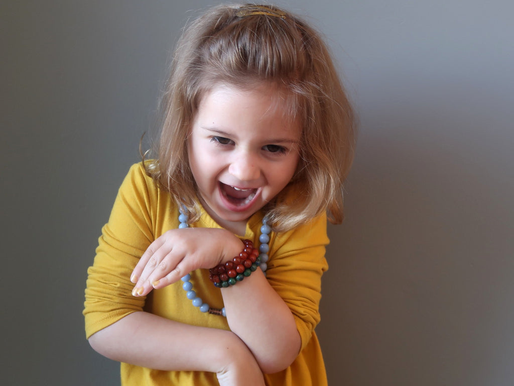 little girl laughing wearing crystal healing jewelry