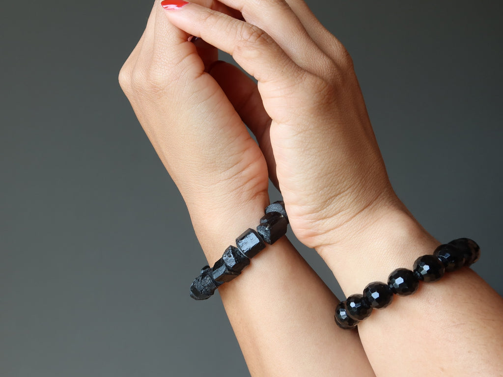 hands wearing raw and faceted black tourmaline bracelets