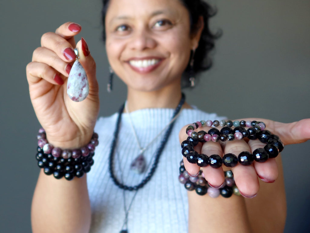 sheila of satin crystals wearing and holding tourmaline jewelry