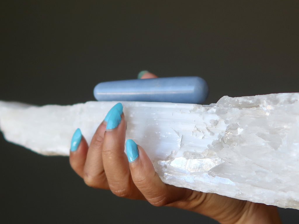 hand holding white selenite stone with blue angelite wand