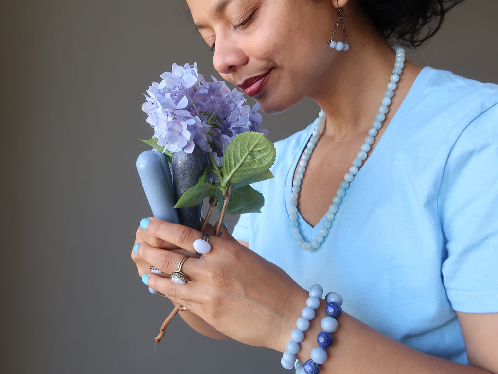 sheila of satin crystals holding a bouquet of flowers and angelite massage wands