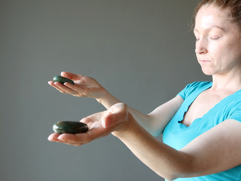 female holding two crystals in her hands meditating